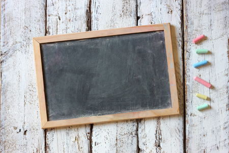 Photo pour top image of chalkboard and colorful chalks over wooden table - image libre de droit