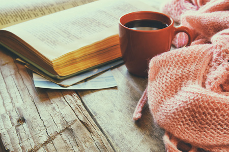selective focus photo of pink cozy knitted scarf with to cup of coffee, wool yarn balls  and open book on a wooden table