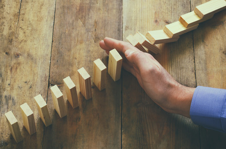 Foto de a male hand stoping the domino effect. retro style image executive and risk control concept - Imagen libre de derechos