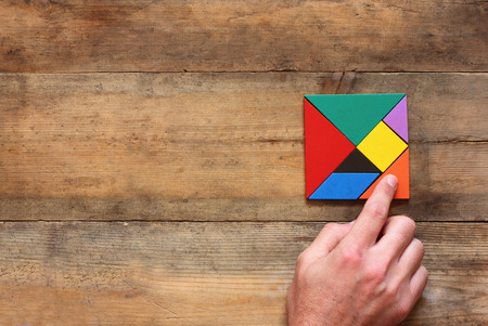 Foto de kid's hand holding a missing piece in a square tangram puzzle, over wooden table. - Imagen libre de derechos