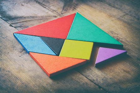 a missing piece in a square tangram puzzle, over wooden table.