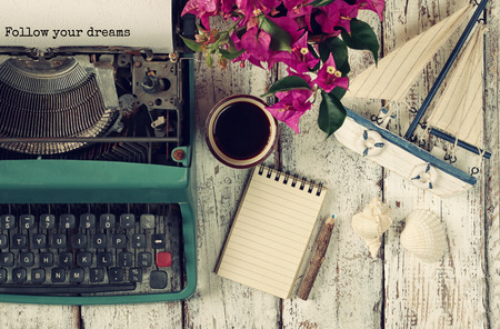 image of vintage typewriter with phrase Follow your dreams, blank notebook, cup of coffee and old sailboat on wooden table