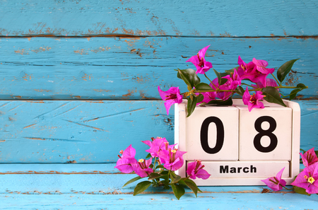 wooden March 8 calendar, next to purple flowers on old blue rustic table. selective focus. vintage filtered