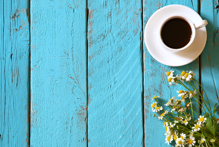 Photo for top view image of daisy flowers next to cup of coffee on blue wooden table - Royalty Free Image