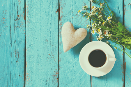 top view image of daisy flowers and fabric heart next to cup of coffee on blue wooden table. vintage filtered and toned