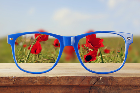 Photo pour hipster glasses on a wooden rustic table in front of the field of red poppies. vintage filtered - image libre de droit