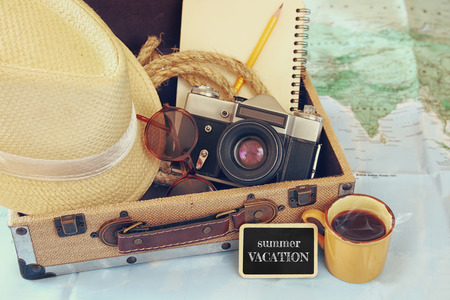 Photo for traveling concept. camera, cup of coffee, sunglasses, fedora hat and notebook. vintage filtered. selective focus - Royalty Free Image