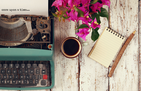 Foto de image of vintage typewriter with phrase once upon a time, blank notebook, cup of coffee on wooden table - Imagen libre de derechos