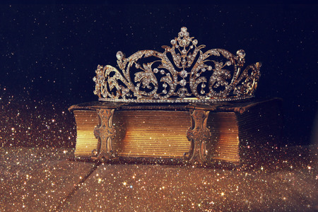 low key image of beautiful diamond queen crown on old book. vintage filtered. selective focus