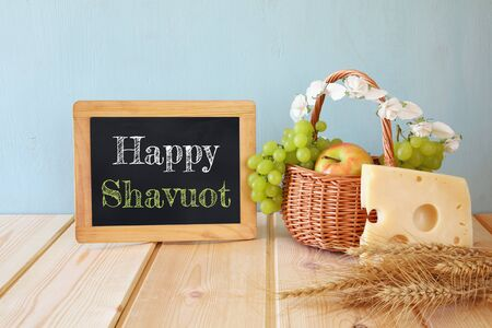 image of dairy products and fruits next to blackboard, on wooden background. Shavuot