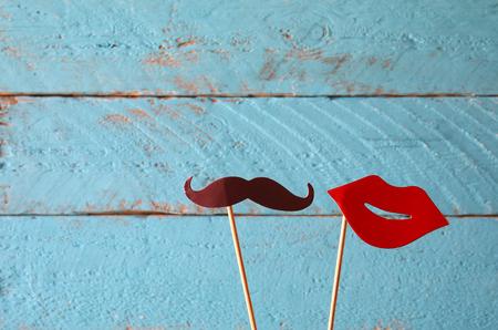 Foto de paper heart shape fake lips and mustaches in sticks in front of wooden background. vintage filtered image - Imagen libre de derechos