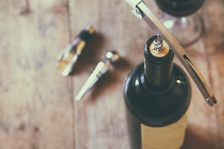 Photo for top view image of red wine bottle and corkscrew over wooden table. retro style image selective focus. - Royalty Free Image