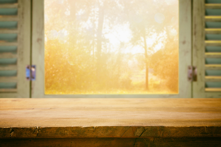 Empty table in front of blurry autumn nature through the window. Ready for product display montage