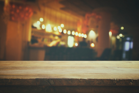 Photo for Image of wooden table in front of abstract blurred background of restaurant lights. Retro filtered - Royalty Free Image