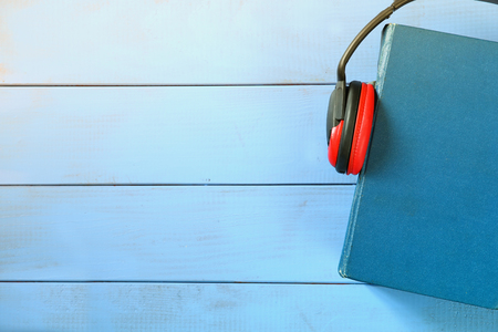Photo pour top view of audio book concept, blue book cover and headphones over wooden table - image libre de droit