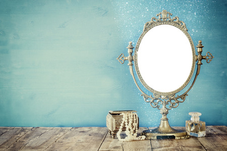 Old vintage oval mirror and woman toilet fashion objects on wooden table. Filtered image