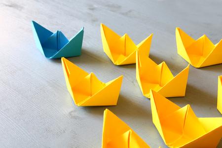 Foto de Leadership concept with paper boats on blue wooden background. One leader ship leads other ships. Filtered and toned image - Imagen libre de derechos