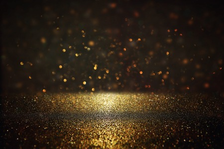 glitter vintage lights background. gold and black. de-focused.