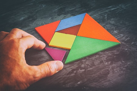 Photo pour man's hand holding a missing piece in a square tangram puzzle, over wooden table. - image libre de droit