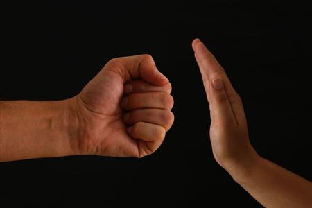 Photo pour Image of male fist and female hand showing STOP. Domestic violence concept against women - image libre de droit