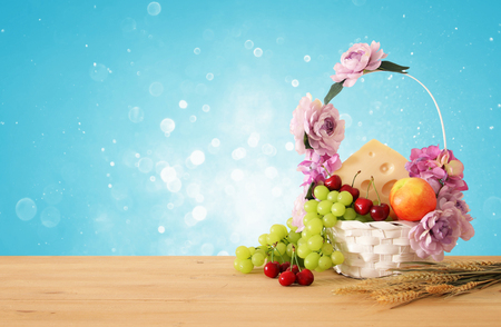 image of fruits and cheese in decorative basket with flowers over wooden table. Symbols of jewish holiday - Shavuot