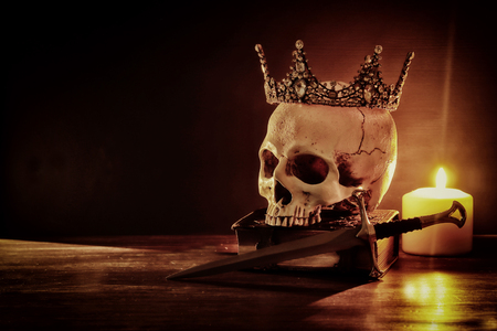 Photo pour Human skull, old book, sword, crown and burning candle over old wooden table and dark background - image libre de droit