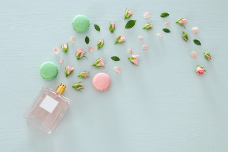 Top view image of perfume bottle with rose petals flowers and macaroon over pastel blue backgroundの写真素材