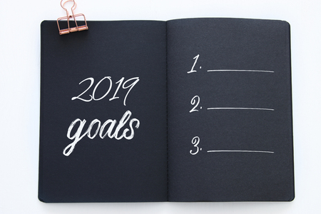 Foto de Top view 2019 goals list with notebook over wooden white desk - Imagen libre de derechos