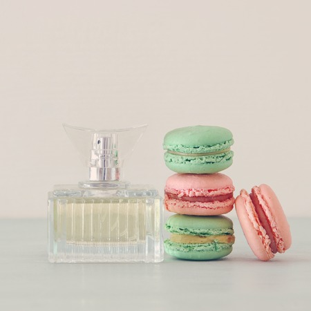 Image of perfume bottle with rose petals flowers and macaroon over pastel tableの写真素材