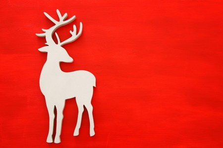Photo pour Top vie image of white wooden christmas deer over red background. Flat lay. - image libre de droit