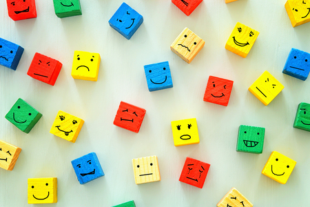 Foto de concept of Different emotions drawn on colorfull cubes, wooden background. - Imagen libre de derechos