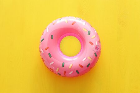 Photo pour Inflatable donut ring over yellow wooden background - image libre de droit