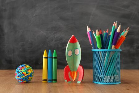 Photo pour Education and back to school concept. Cardboard rocket and pencils in front of classroom blackboard - image libre de droit