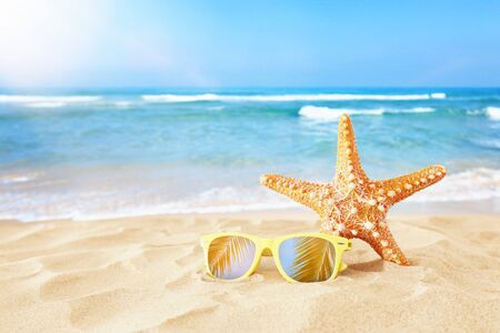 Photo pour Holidays. Sand beach, sunglasses and starfish in front of summer sea background with copy space - image libre de droit