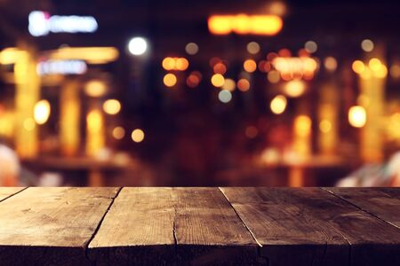 Photo pour Background of wooden table in front of abstract blurred restaurant lights - image libre de droit