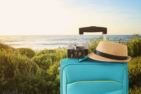 Foto für Recreation image of traveler luggage, camera and fedora hat infront of a rural lanscape. Holiday and vacation concept - Lizenzfreies Bild