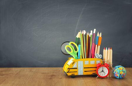 Foto de Education and back to school concept. Pencils stand as bus over wooden desk infront of classroom blackboard - Imagen libre de derechos
