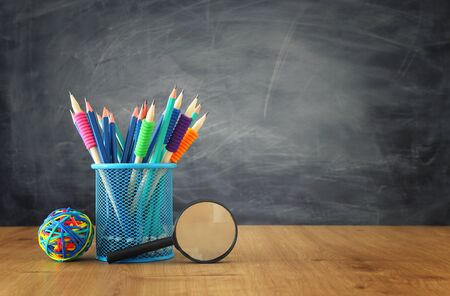 Photo for Education and back to school concept. Stationery over wooden table in front of classroom blackboard - Royalty Free Image