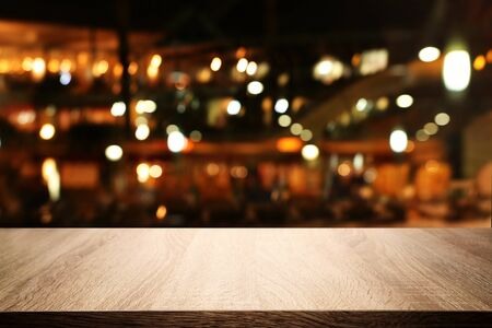 Photo for background Image of wooden table in front of abstract blurred restaurant lights - Royalty Free Image