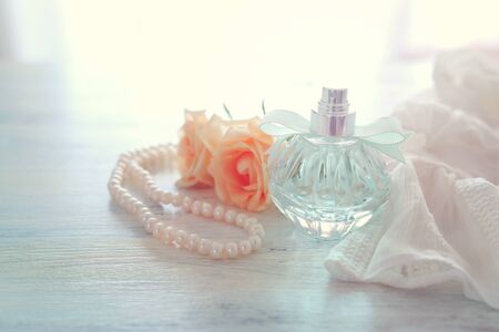 beauty/fashion Image of elegant perfume bottle, white pearls and delicate roses over pastel background. vintage filtered imageの写真素材