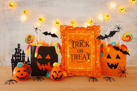Photo for holidays image of Halloween. Pumpkins, bats, treats, paper gift bag over wooden table - Royalty Free Image