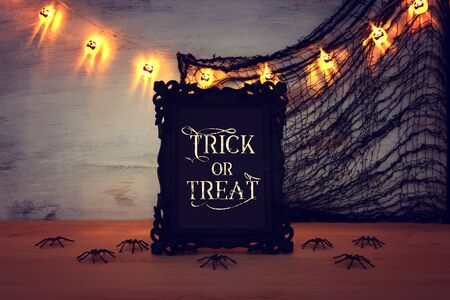 Photo for holidays image of Halloween. photo frame with text over wooden table - Royalty Free Image