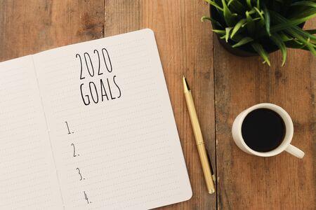 Foto de Business concept of top view 2020 goals list with notebook, cup of coffee over wooden desk - Imagen libre de derechos