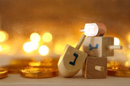 Photo for religion concept of of jewish holiday Hanukkah with wooden dreidels (spinning top) and chocolate coins over wooden table and bokeh lights background - Royalty Free Image