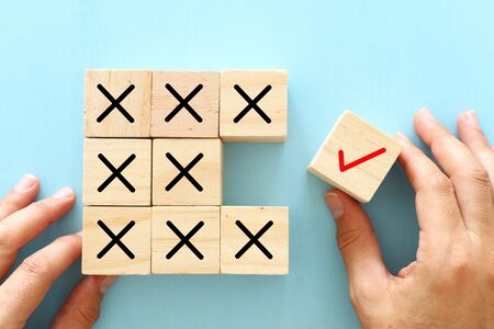 Photo pour A hand chooses a cube with check mark symbol instead of cubes with cross sign. An idea of positive thinking and change of mind - image libre de droit