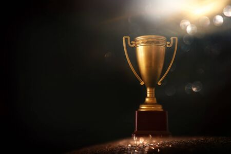 Photo for low key image of trophy over wooden table and dark background, with abstract shiny lights - Royalty Free Image
