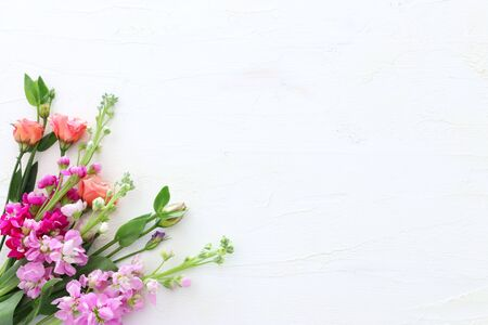 Photo for spring bouquet of pink flowers over white vintage wooden background. top view, flat lay - Royalty Free Image