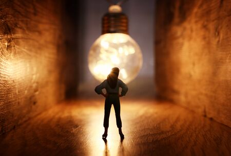 Photo for Surreal image of person in dark corridor looking at glowing light bulb. Concept of finding the right idea, or way out - Royalty Free Image