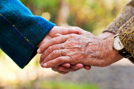Elderly couple holding hands outdoors