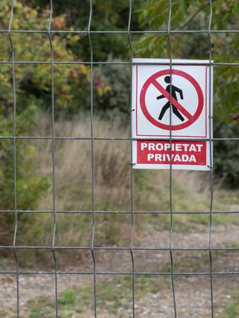 Warning sign on a metal fence with the Spanish text 'private terrain' and the corresponding symbol.
